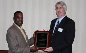 Photograph: Steve Toth (right) presenting plaque to Dr. Godfrey Nalyanya (left) during awards luncheon at annual meeting of the Southeastern Branch of the Entomological Society of America in Atlanta, Georgia. Photograph by Rosemary Hallberg.