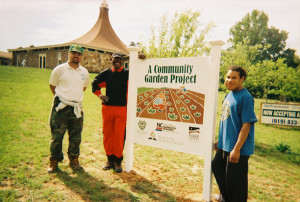 Three people standing by community garden project sign
