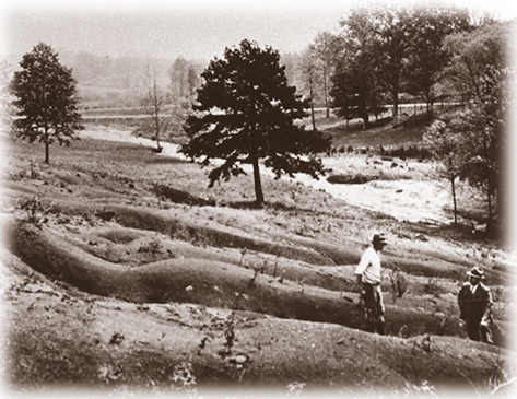 """Old worn-out soils"": Soil erosion was a high-priority agricultural issue that Extension addressed early on. Here, an agent and farmer inspect a seriously eroded field in the late 1920s."