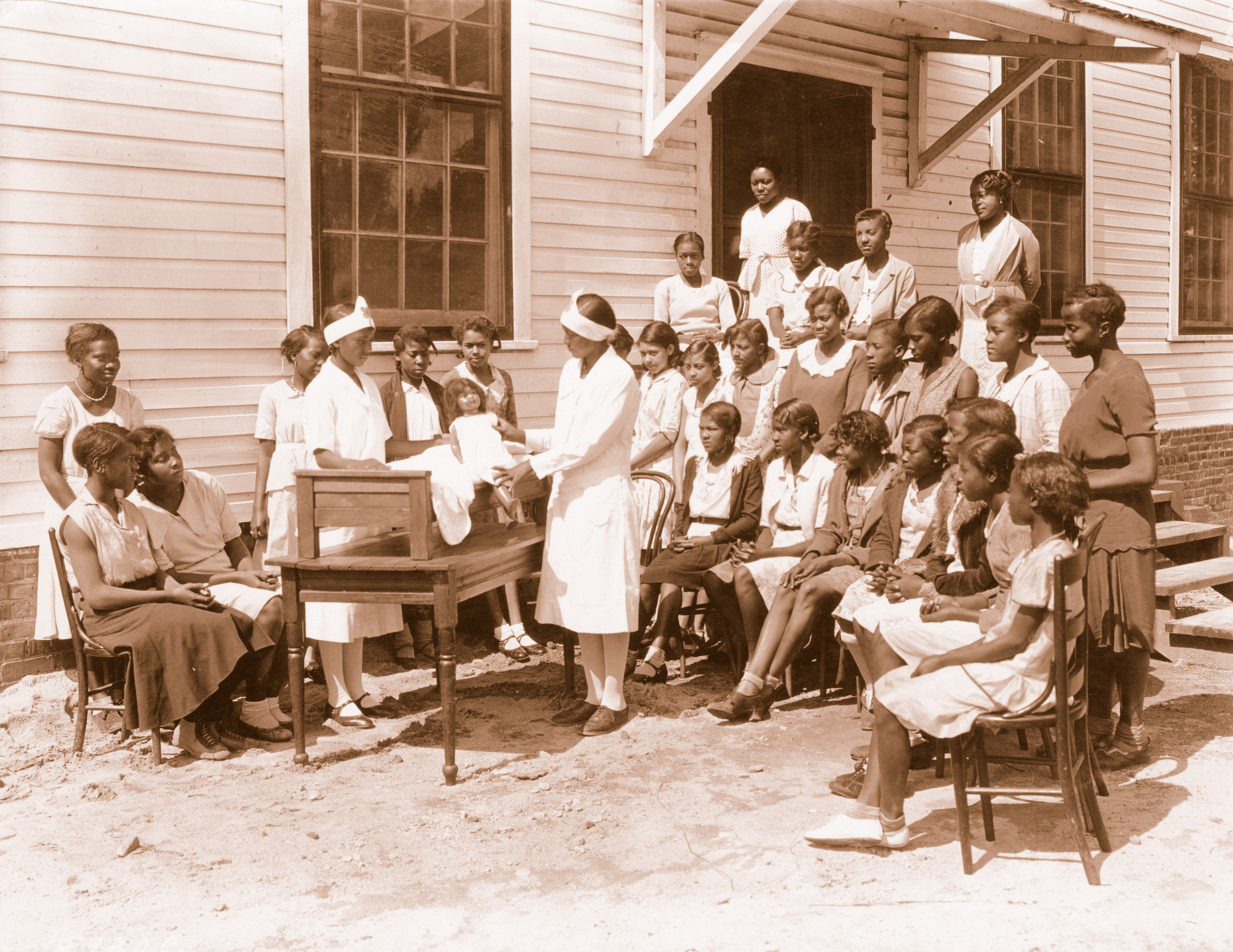 An Extension home demonstration agent discusses child care skills with a group of girls around 1930.