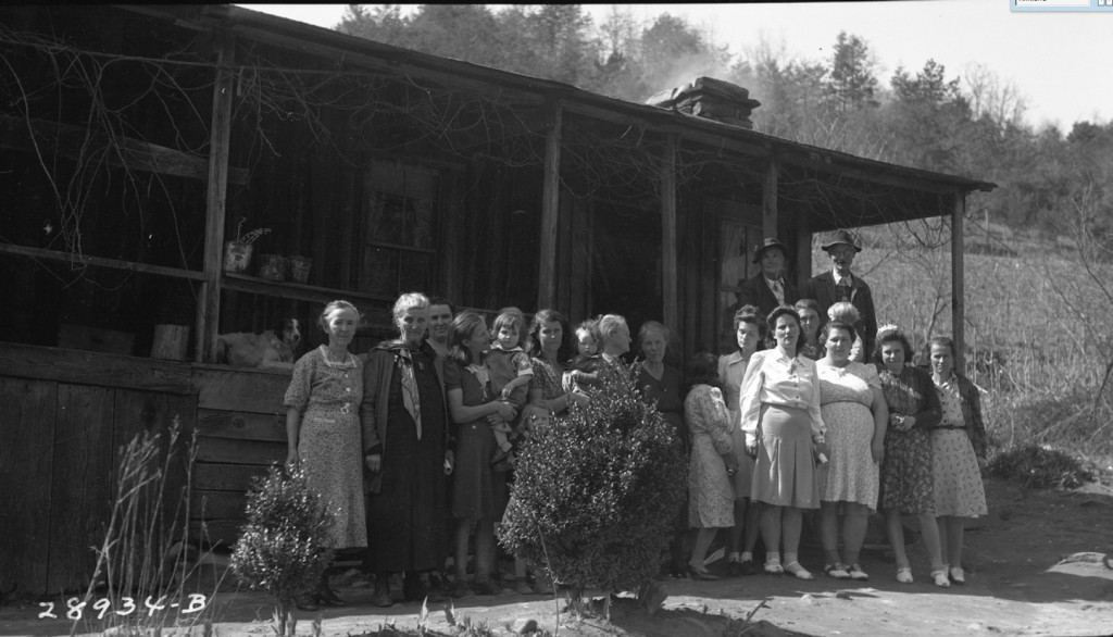 A group of ladies gathered for a canning demonstration at Roxie McClure's home. Pictured: Lou Chambers, Martha Anthony, Lydia Crisp, Maudie Earley with daughter, Ida Kirkland with daughter, Grandmother Woody, Mary Crisp, Tina Kirkland, Kate Shook, Mossie Kirkland, Hattie Kirkland with son, Hazel McClure, Edna Anthony, Allie Anthony. Back row: John Chambers (Along the River: People and Places ~ Duane Oliver)