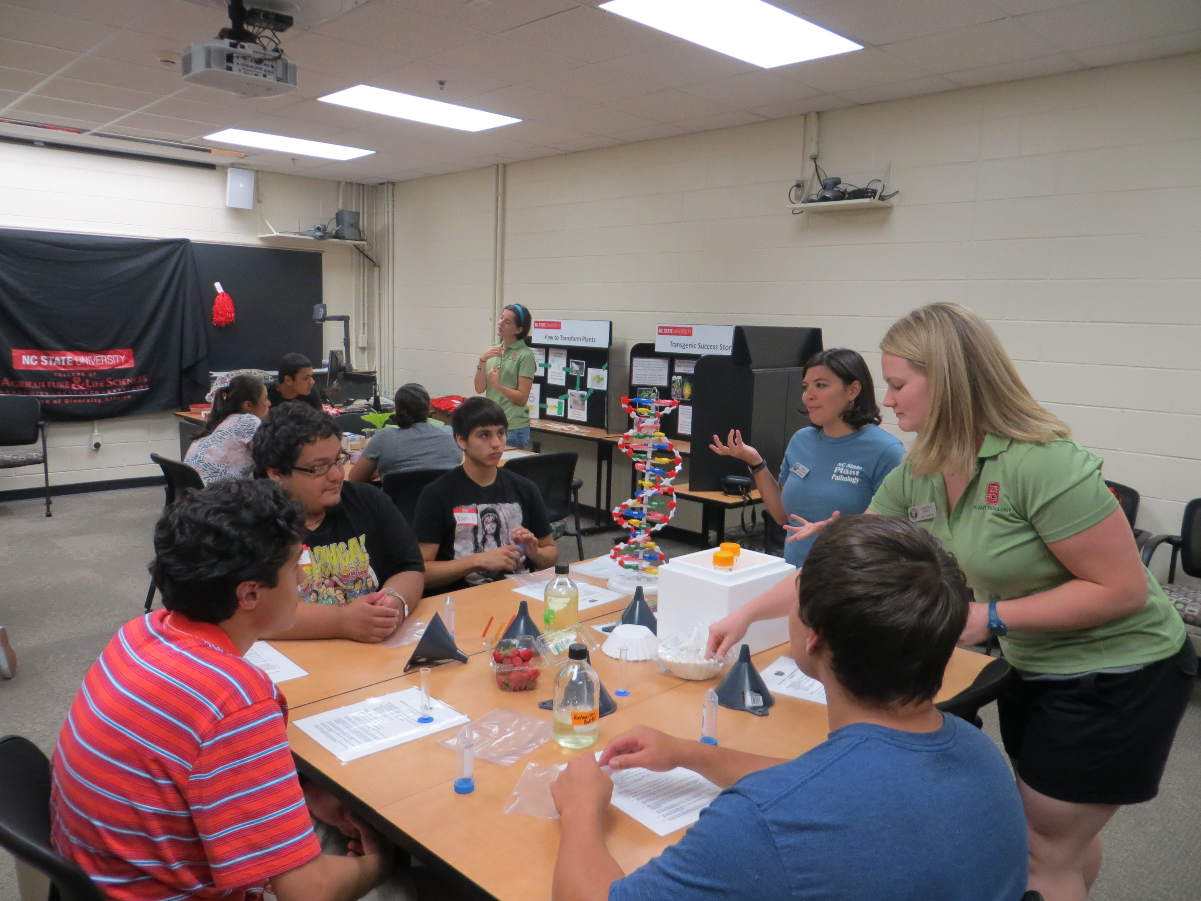 Plant Pathology Graduate Students Emma Lookabaugh and Laura Bostic teach high school students about DNA before diving into a strawberry DNA extraction. Photo Credit: Alyssa Koehler.