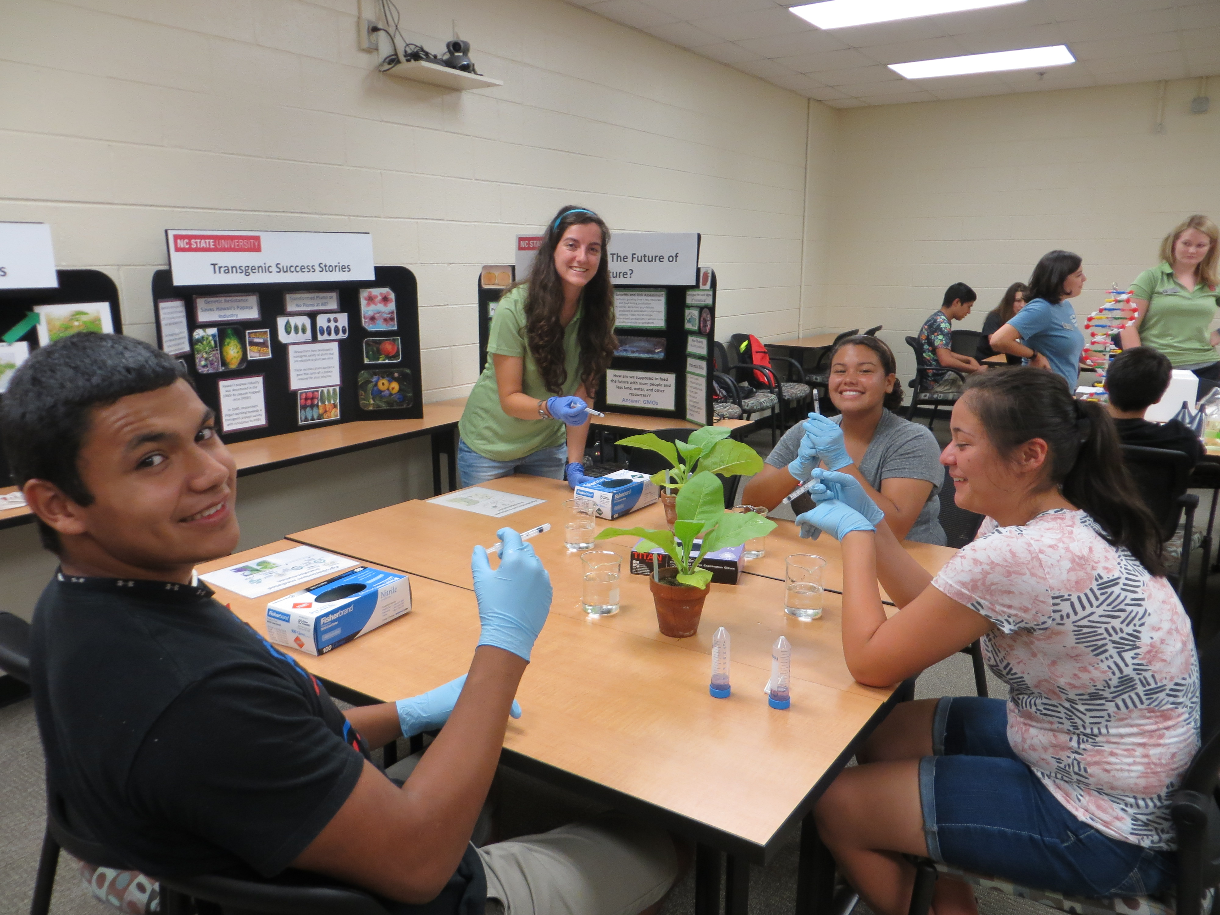 Graduate Student Emma Wallace demonstrates a plant transformation. Photo Credit: Alyssa Koehler.