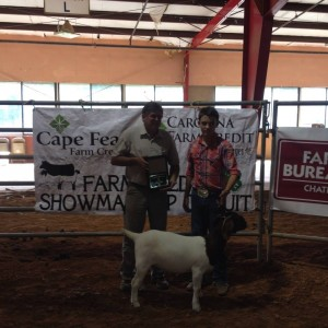 Coleman Berry won many of the top awards this past weekend at the Chatham County Livestock Show. He is shown here with judge, Ron Hughes.