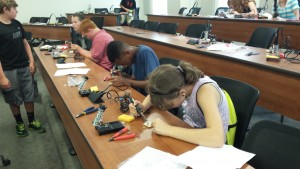 4-Hers at work soldering soil monitoring testers.