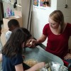 4-H Agent, Laura Oliver, helps 2nd graders at Pines handle chicks.