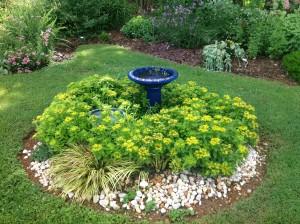 Small garden with birdbath and flowers
