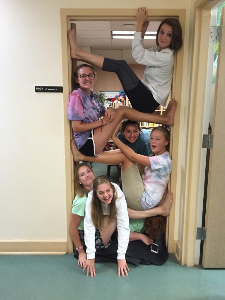 TiLT youth volunteers doing Yoga in the door-way before teaching