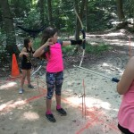 Aiva Nolan learns how to use a bow and arrow during archery.