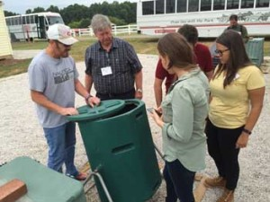 workshop participants look over a compost bin