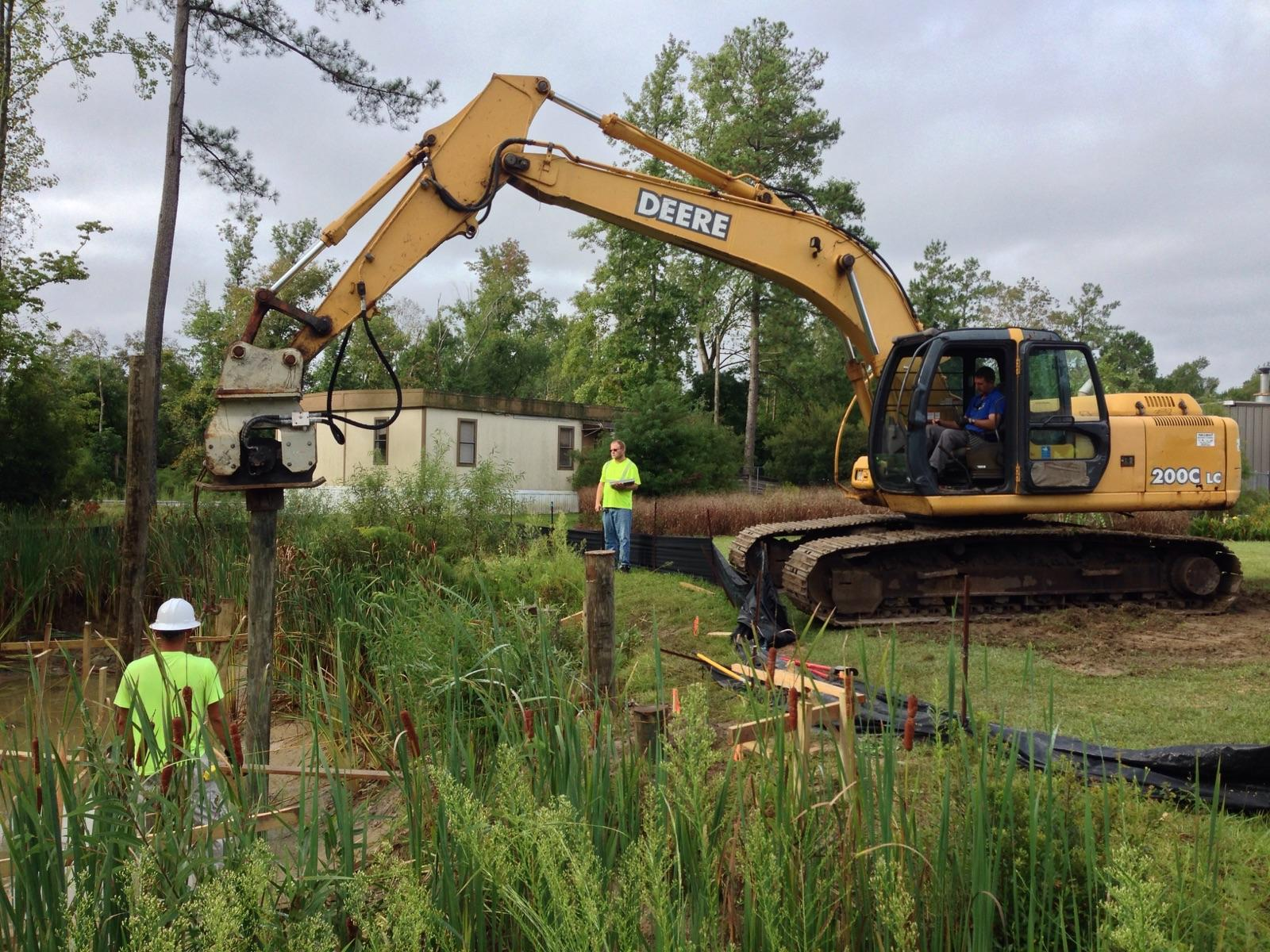 construction workers drive the pilings that will support the summer house in the discovery gardens - Dicovery Garden