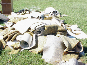 Water-logged carpet piled in front of a house.