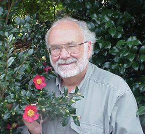 Dick Bir standing by flowering shrub