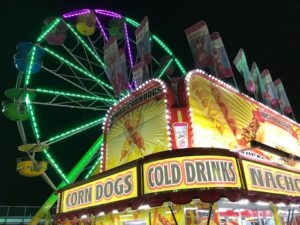 corner of food stand advertising corn dogs, cold drinks and nachos with lit up ferris wheel in background