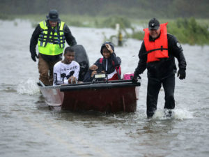 Volunteers from the Civilian Crisis Response Team help rescue three children from their flooded home September 14, 2018 in James City, North Carolina.