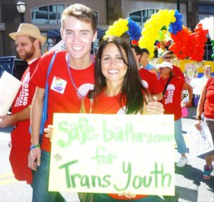 "Austin and Maru holding a sign that read, ""Safe bathrooms for trans youth"""