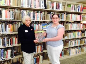 Astrid Ewing presenting a copy of the NC Extension Gardener Handbook to the Hendersonville Public Library