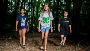 Three children walking toward the camera side-by-side in the forest as part of an Extension 4-H program