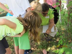 EMG volunteer teaching kids about plants.