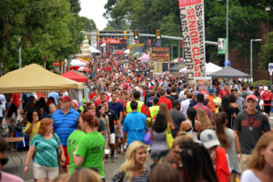 A crowd of people line the street during a public event at NC State University
