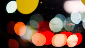 Street lights and car lights at night are distorted to look like big glowing balls of color in red, white and yellow