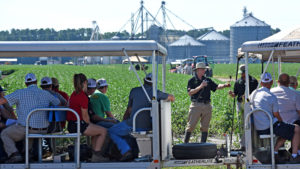 An NC State Extension specialist talking into a microphone in a soybean field while giving a tour to participants sitting in a tram.