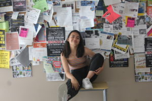 The author is sitting on a stool. Many different papers and advertisements are hung up behind her.