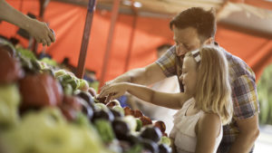 A smiling bearded man and his daughter buying fresh produce at an outdoor farmers market booth.