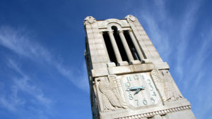 The NC State University Memorial Belltower is show close up, focusing on the clock with a bright blue sky in the background.