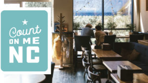 Count On Me NC program logo beside a photo of a cafe with two people sitting at a table by the window