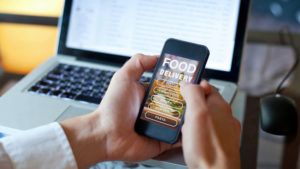 A pair of hands are holding a cell phone with a food delivery app open on the screen - an open laptop is in the background.