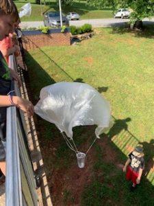 Boy throwing homemade parachute