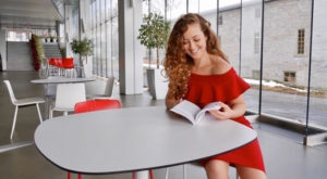 Young woman in red dress sitting at a white table reading a book