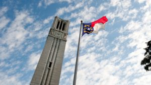 The North Carolina flag atop a flag pole beside the NC State University belltower, with a blue sky and white clouds above.