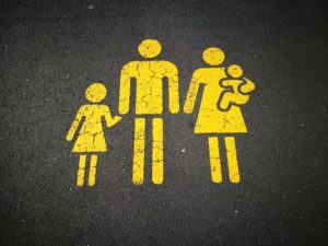 Stenciled image of family, yellow paint on concrete