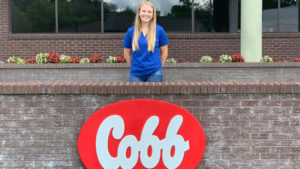 Sophie Chance standing behind the red and white Cobb sign