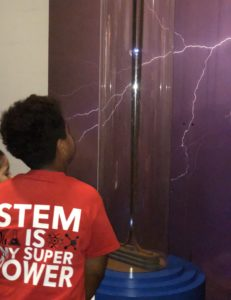 While in shirt reading STEM is my superpower gazes at an electricity experiment