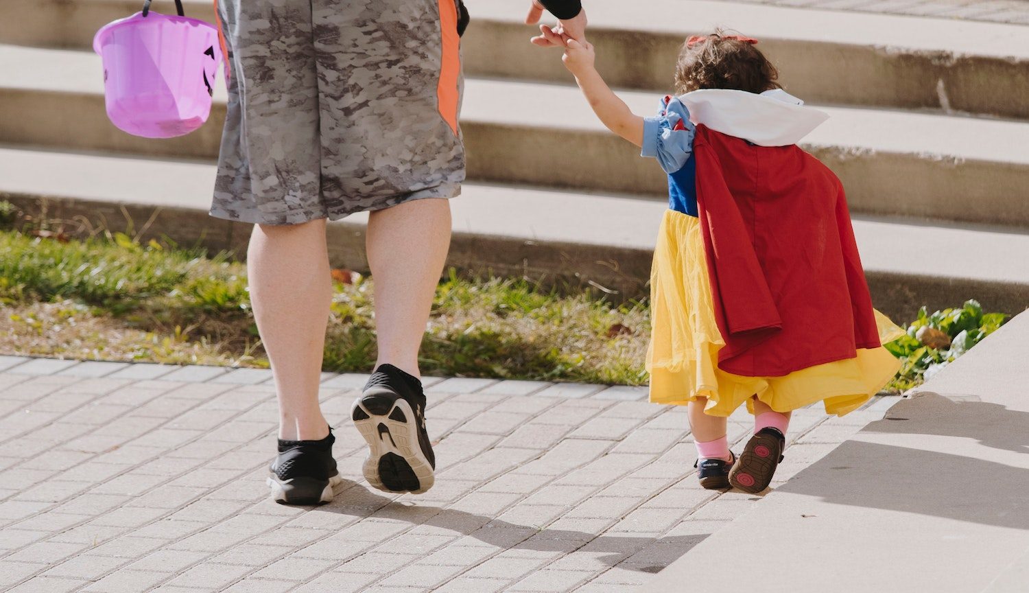Child in costume holding an adult's hand