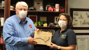 Karen Beck and Steve Troxler in masks holding a plaque