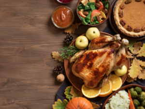 Holiday meal of whole cooked chicken garnished with orange slices and apples surrounded by side dishes and pumpkin pie.